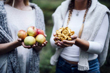 Midsection of women holding apples and chanterelles outdoors