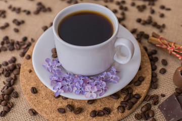 Coffee cup with lilac and wood plate.