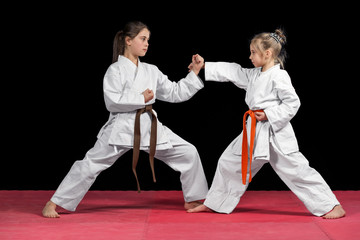 Two girls in kimono are training paired exercises karate