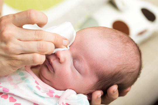 Mother cleaning eyes of a newborn baby with physiological soluti