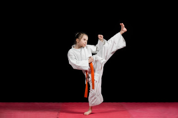 Little girl practice karate isolated on black