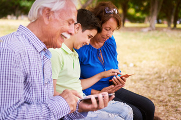 Child Helping Grandma Text Messaging On Mobile Phone