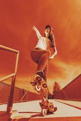 Teenage girl skater riding skateboard on street.
