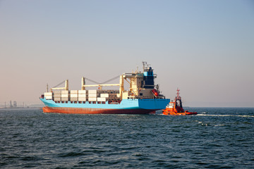 Container ship arriving at port, assisted by tugboat.