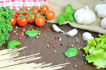 Tomatoes, spaghetti (pasta), parsley and garlic on wooden table