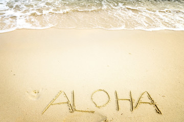 Inscription Aloha written on the sandy beach with ocean wave - free space. vintage color tone effect