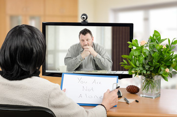 Depressed man in monitor of psychotherapist