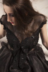 Portrait of beautiful young brunette woman princess in black dress lying down on floor