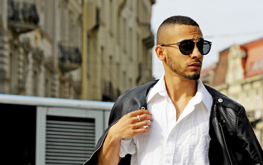 Fashion stylish young african man in sunglasses and black rock leather jacket.