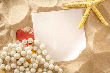 Pearl, seashells and paper on sand