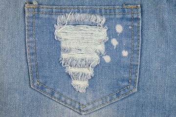 Blue jeans background closeup view to torn texture.