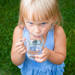 Child drinking water outdoors