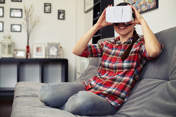 Woman holding virtual reality headset glasses and smiling