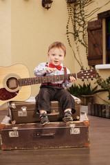 Portrait of a romantic little boy sitting with guitar.