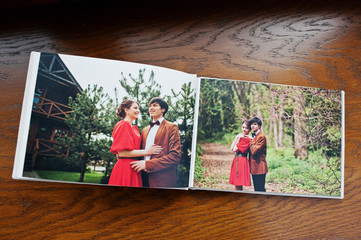 Open pages of album photobook couple in love on wooden backgroun