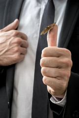 Butterfly sitting on businessman's thumb