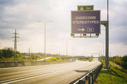 Empty highway and traffic sign above it. Text Overcome Stereotypes - appeal to avoid stereotypes, prejudice and generalization. Sunny positive atmosphere