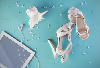 White shoes and computer with earphone on the blue background