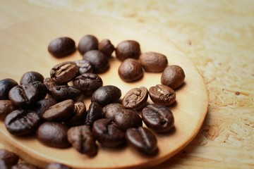 coffee beans on background of brown wood.
