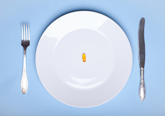 One pill on white dinner dish with flatware on blue background