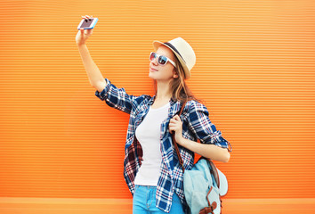 Fashion pretty woman makes selfie portrait on smartphone over co