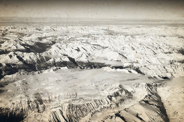 Aerial view of snowy Alps mountains. Old photo effect applied.