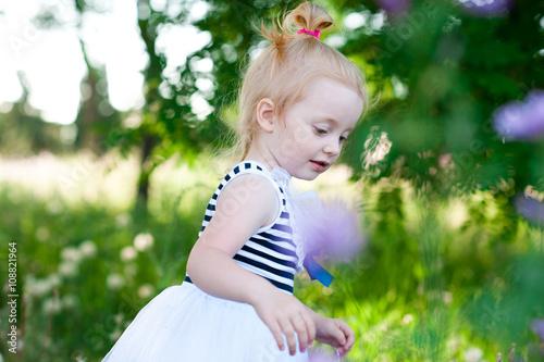 469dfdb3e Cute kid girl 2-3 year old playing outdoors. Wearing stylish striped ...