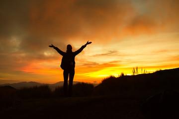 Enjoying the great outdoors! Female hiker celebrating during a beautiful sunset.
