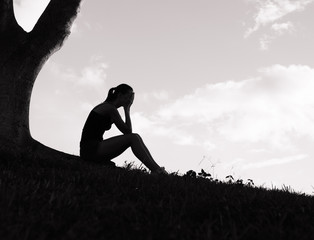 Sad female sitting under a tree.