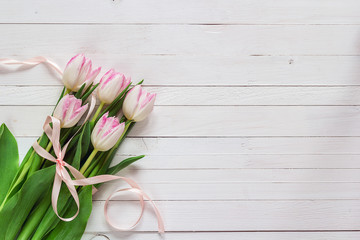 Bouquet of pink tulips with pink ribbon on white painted wooden