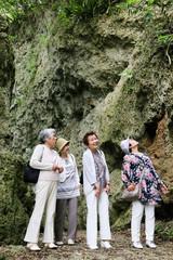 岩場を歩いている高齢者女性4人