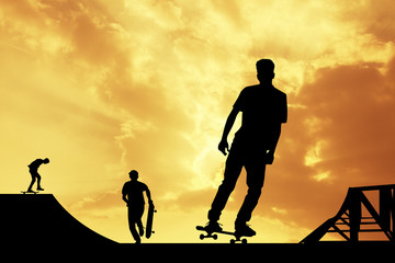 boys with skateboarders at sunset