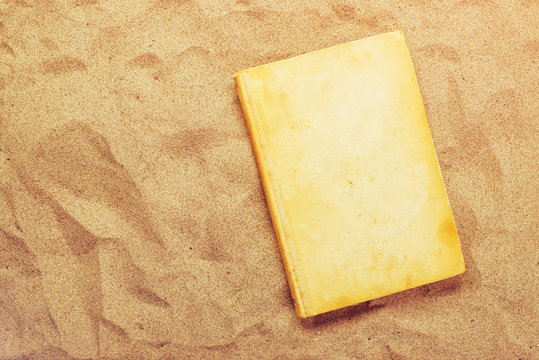 Reading favourite classic old book on summer vacation beach holi