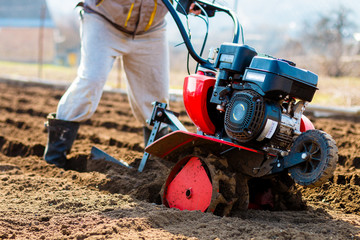 Man working in the garden with Garden Tiller. Garden tiller to work, closeup. Man with tractor cultivating field at spring