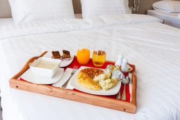 Breakfast set  in wooden tray serving on bed