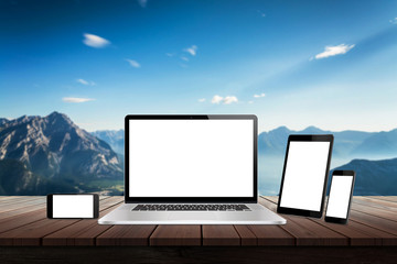 Laptop, tablet and smart phone responsive display devices on table. Isolated white screen for mockup presentation. Mountain nature landscape in background