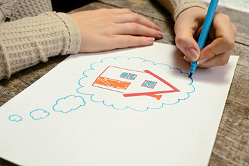 A woman hand with pencil is drawing picture of country house