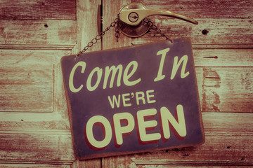 Come In We're Open on the wooden door, retro vintage style