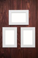 Three empty frames on brown wooden desk