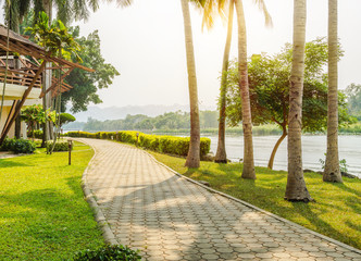 Waterfront walkway with green bush, trees and sun light