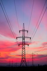High voltage electricity pylon system on sunrise background