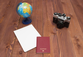 empty notepad, camera, globe and passport on brown wooden background