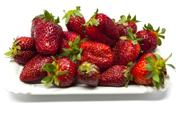 Fresh strawberries on a plate on white background