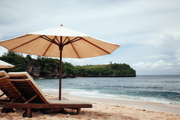 chairs and white umbrella on the beach. Banner
