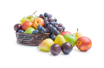 Fruits arrangement. Mix of various fresh ripe fruits plums apples pears peaches and grapes  placed in a wicker basket and around isolated on a white background.