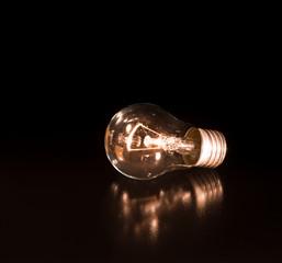 orange incandescent lamp bulb lie on the black mirror