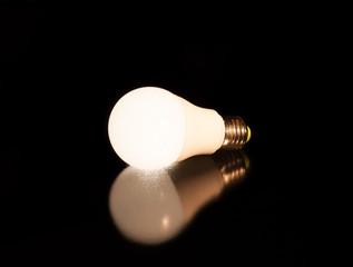 white led bulb lie on the black mirror