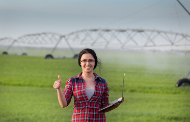 Farmer girl with laptop in front of irrigation system on field