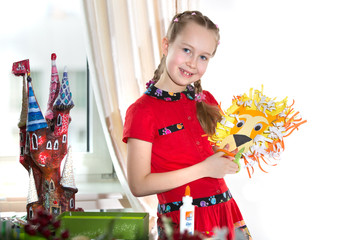 Little girl demonstrating her art craft works, Paper masher fairy castle and Lion mask. Educational and creative concept.