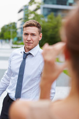 Woman taking pictures of man with smartphone